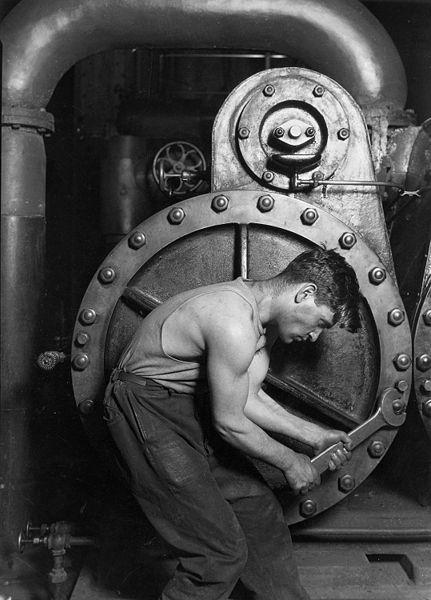 Trabajador mecánico ajustando una máquina de vapor. Fotografía de Lewis Hine, 1920